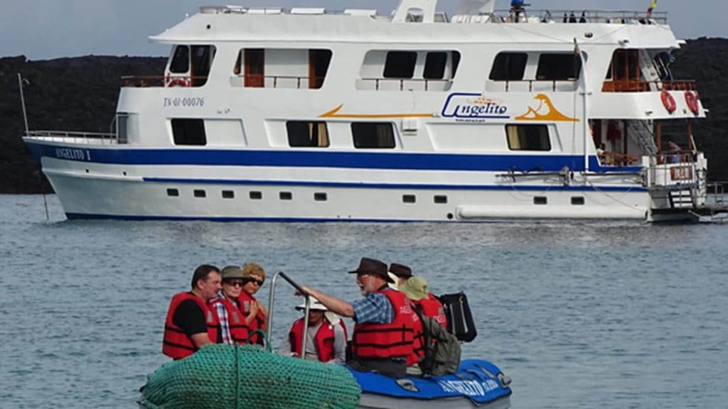 Angelito yacht Galapagos cruise - Tourists with guide in panga boat in front of Angelito yacht