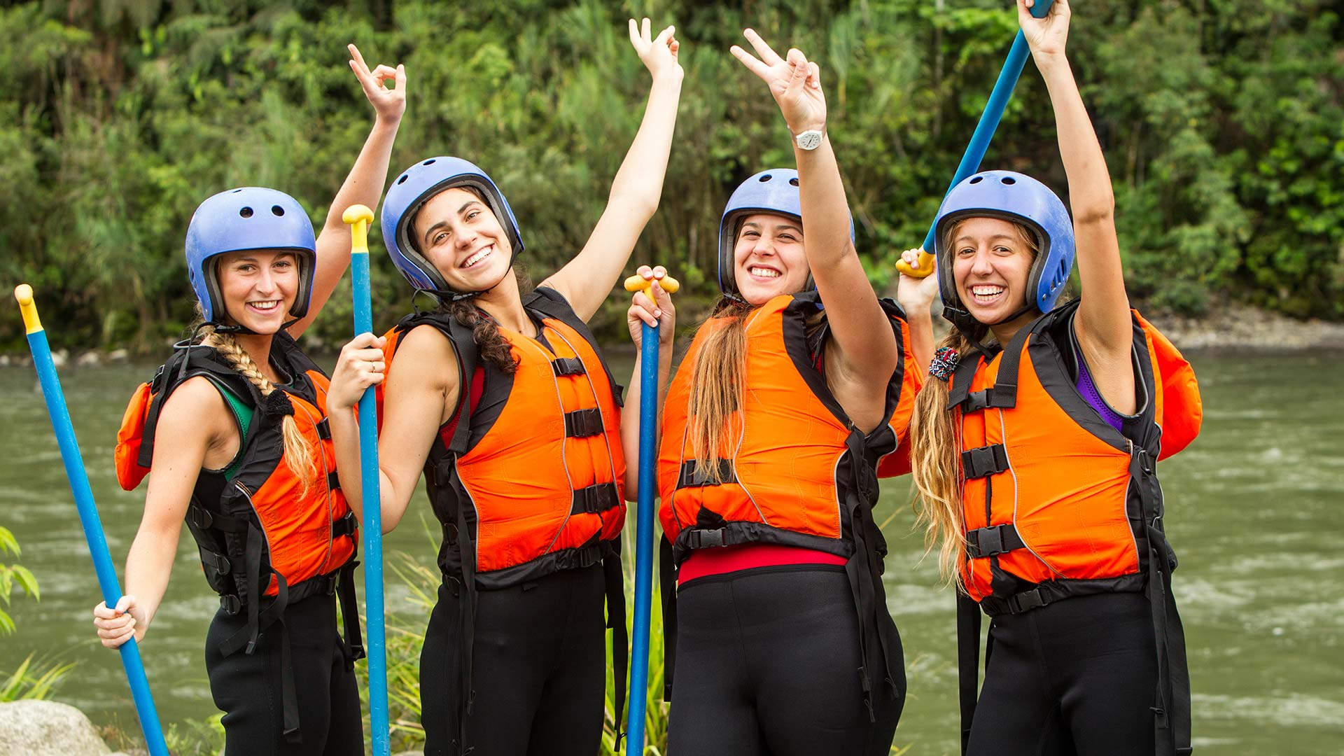 happy rafting tourists celebrate with lifejackets