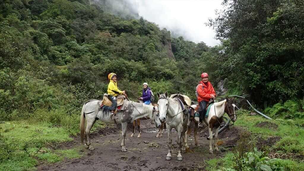 3 tourists enjoy a horse riding tour in the Baños moutains - Ecuador