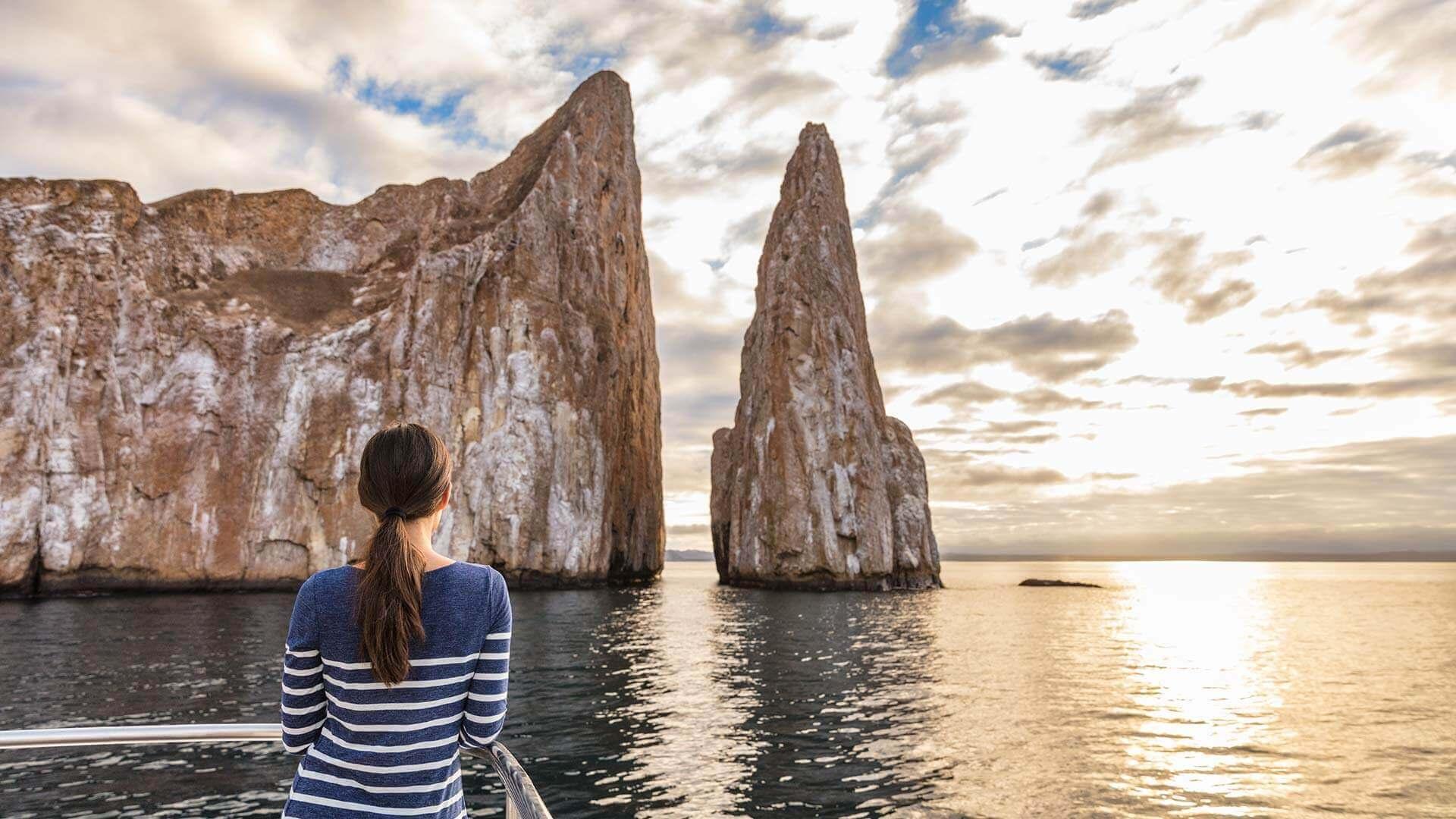 galapagos tourist admires the view of kicker rock leon dormido at san cristobal island