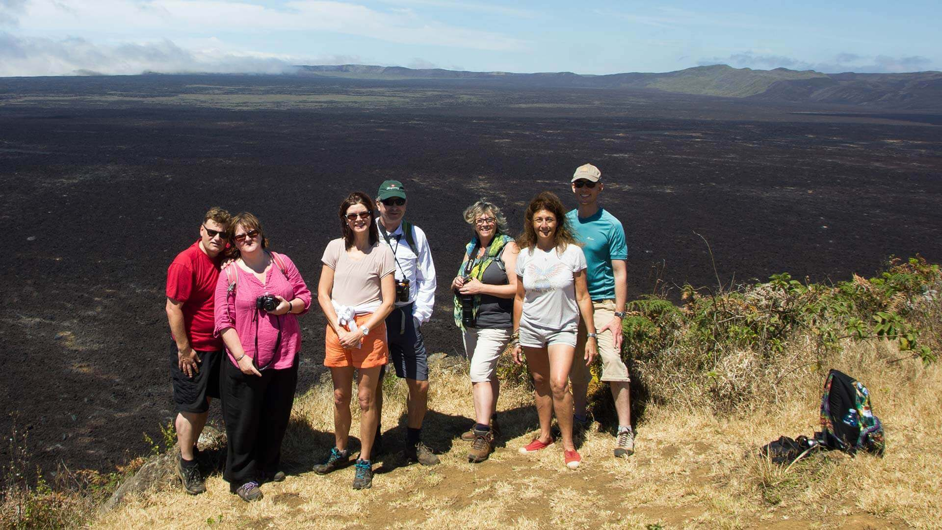 group of tourists pose in front of sierra negra volcano crater isabela galapagos