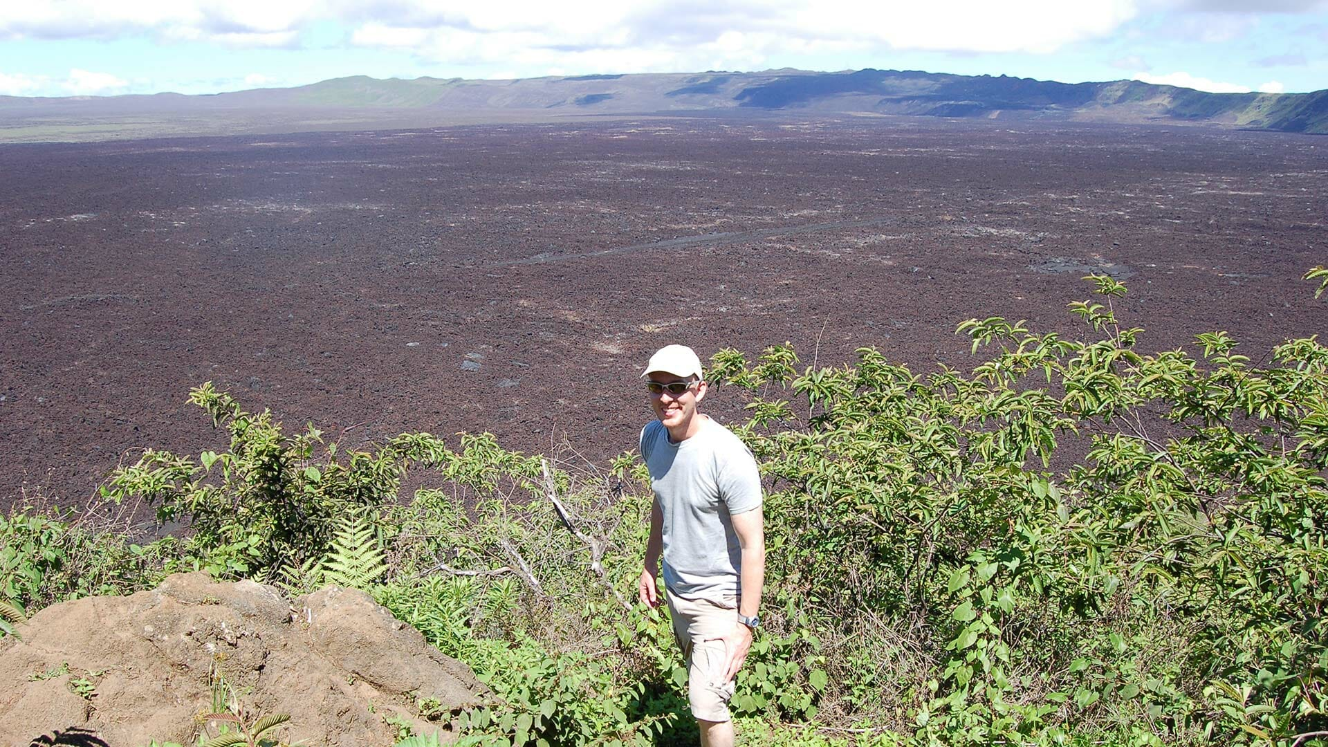 tourist standing in front of sierra negra volcano crater isabela galapagos
