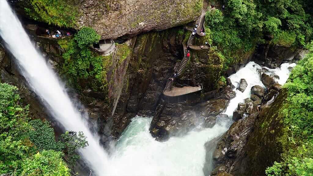 Tourist gets close to Pailon del diablo waterfall via the lookouts, Baños, Ecuador