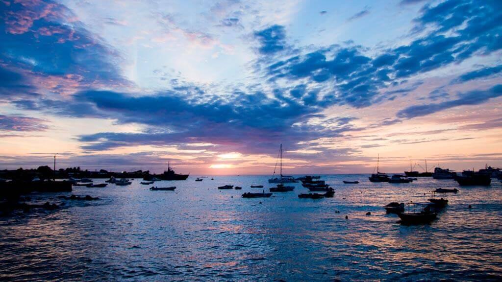 sunset silhouettes of galapagos yacht at puerto aypra harbor santa cruz island
