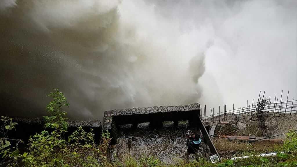 A tourist gets sprayed by Pailon del diablo waterfall, Baños, Ecuador