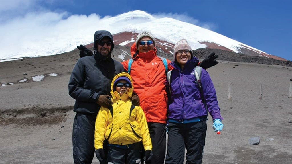 family dressed in warm jackets at cotopaxi volcano national park ecuador
