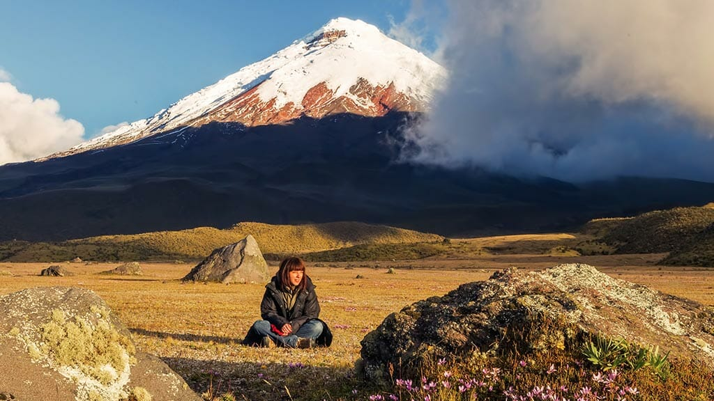 a woman sitting alone on the cotopaxi paramo with a panoramic view of ecuador's cotopaxi volcano behind