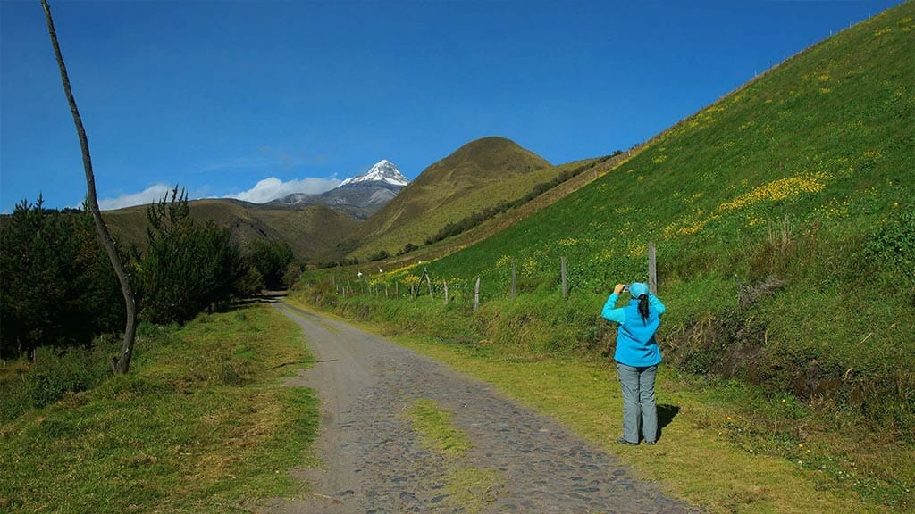 woman taking photo of illinizas volcano peak ecuador