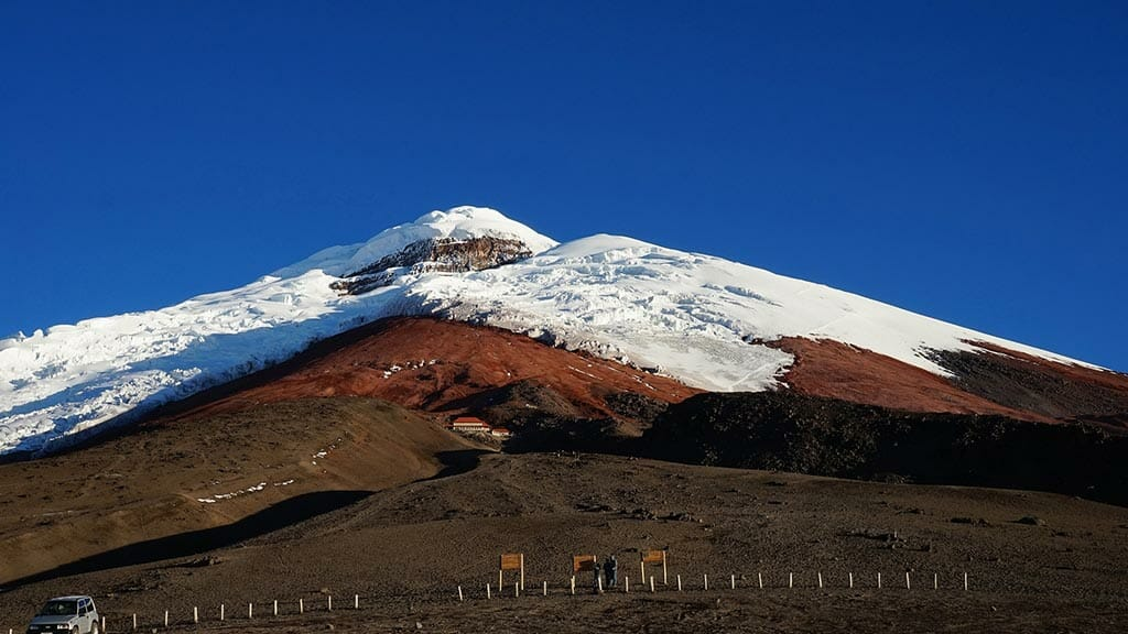 view of snow capped cotopaxi glacier with blue sky from the parking lot