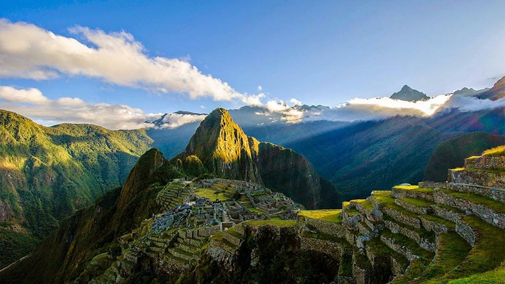 sunny landscape of machu picchu and green surrounding mountains