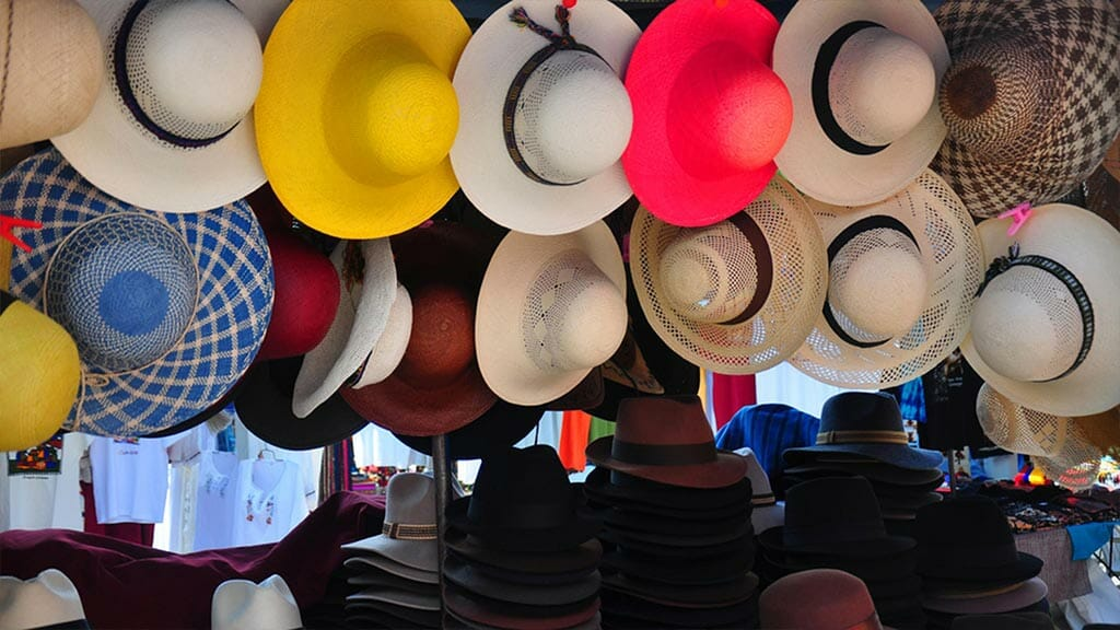 Straw hats hang from a market stall at the Otavalo handicrafts Market - Ecuador