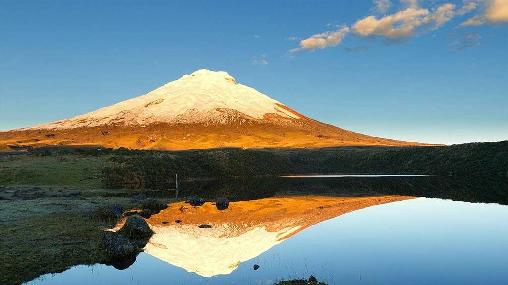 cotopaxi ecuador glowing at sunset with reflection in lake limpiopungo