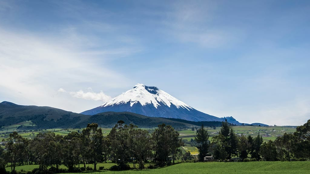 panorama of cotopaxi volcano ecuador with green fields and trees