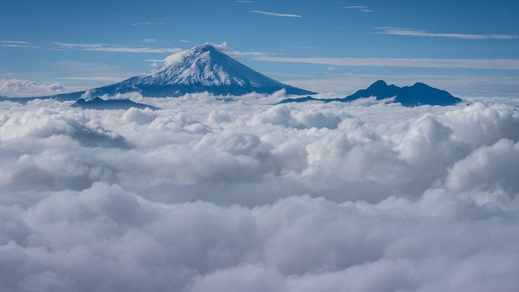 peak of cotopaxi volcano above a carpet of clouds