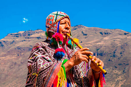 indian man in peru playing flute dressed in colorful poncho