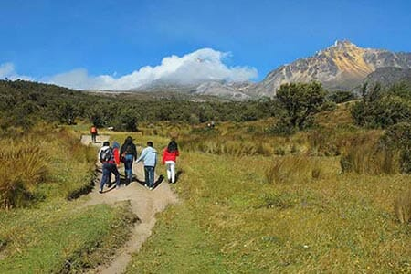 group of tourists treking towards illinizas volcano ecuador