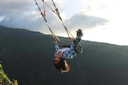 girl swinging upside down swing at the end of the world banos ecuador