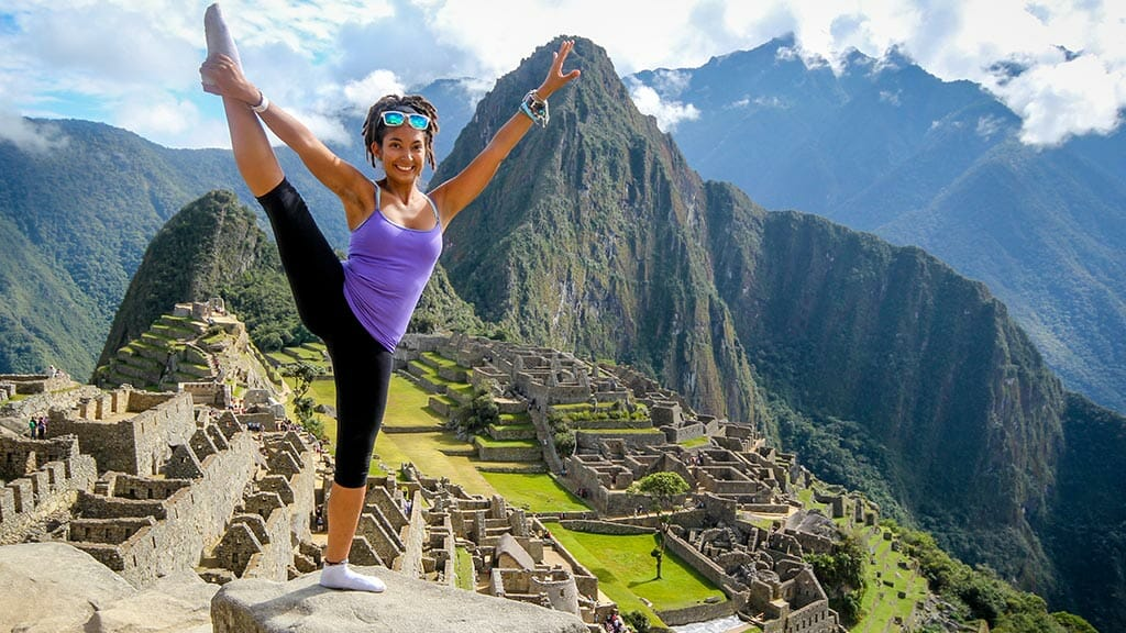 girl doing a yoga pose at machu picchu ruins peru