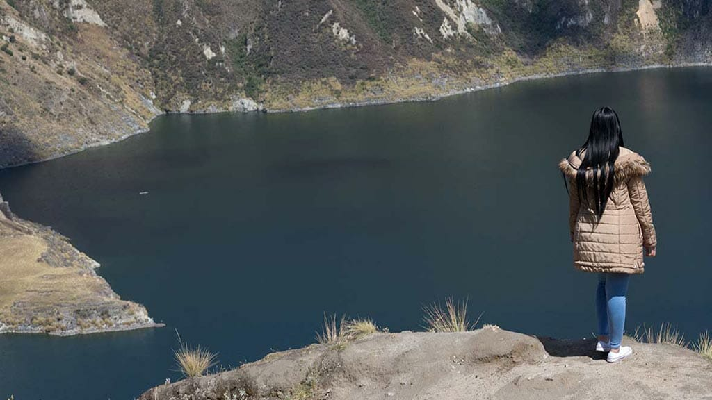 female tourist posing in front of quilotoa lagoon