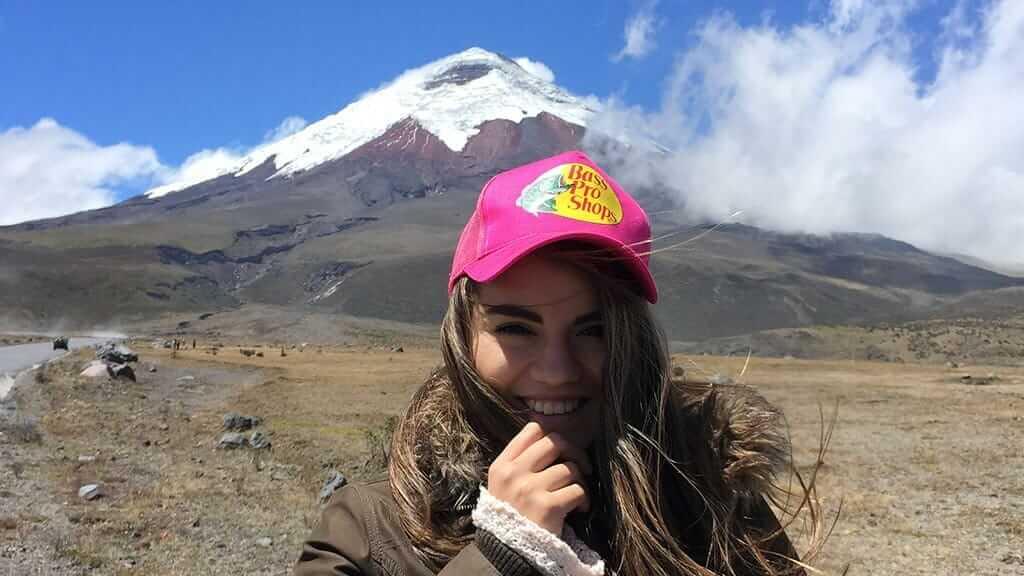 tourist posing in front of ecuador's cotopaxi volcano