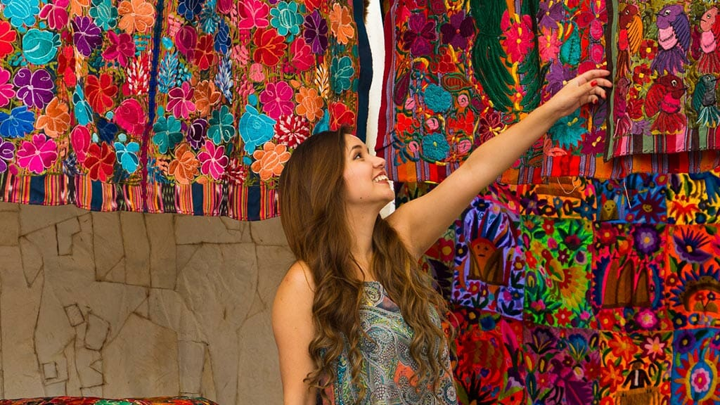 tourist girl admiring colorful traditional fabrics at otavalo market