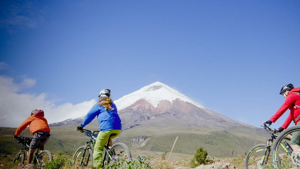 group-of-bikers-with-the-cotopaxi-volcano-panoramic-picture