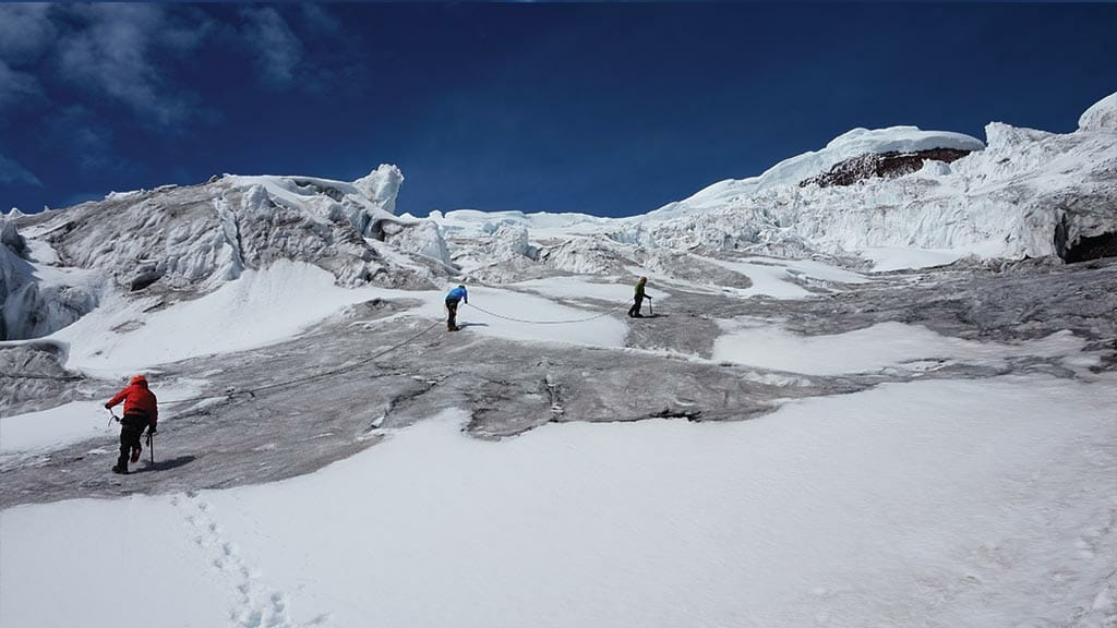 group of climbers roped together heading to cotopaxi summit ecuador