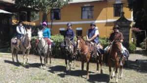 horse riders mounted and ready at la agria hacienda ecuador