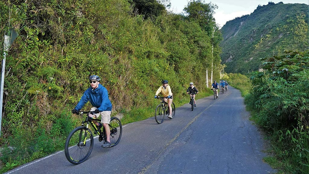 group of tourists biking down the road in ecuador
