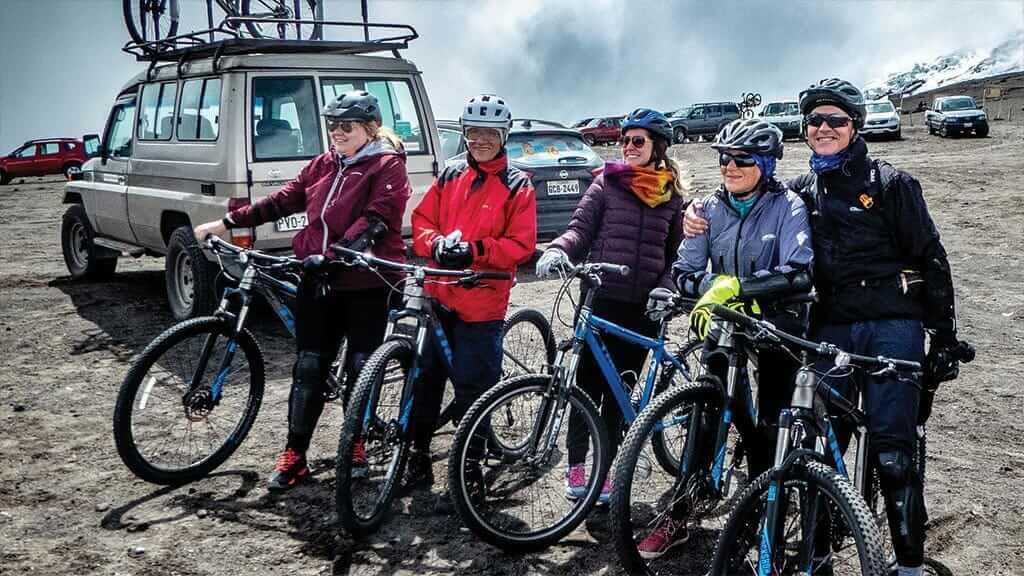 group of tourists with bikes on a cotopaxi biking tour ecuador