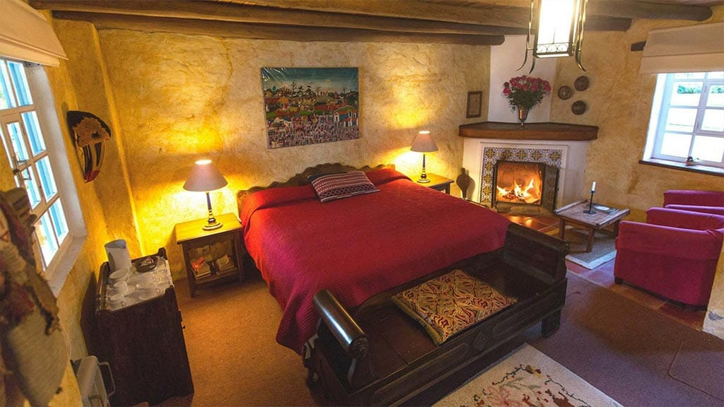 hacienda cusin ecuador - double bed guest room with open fireplace