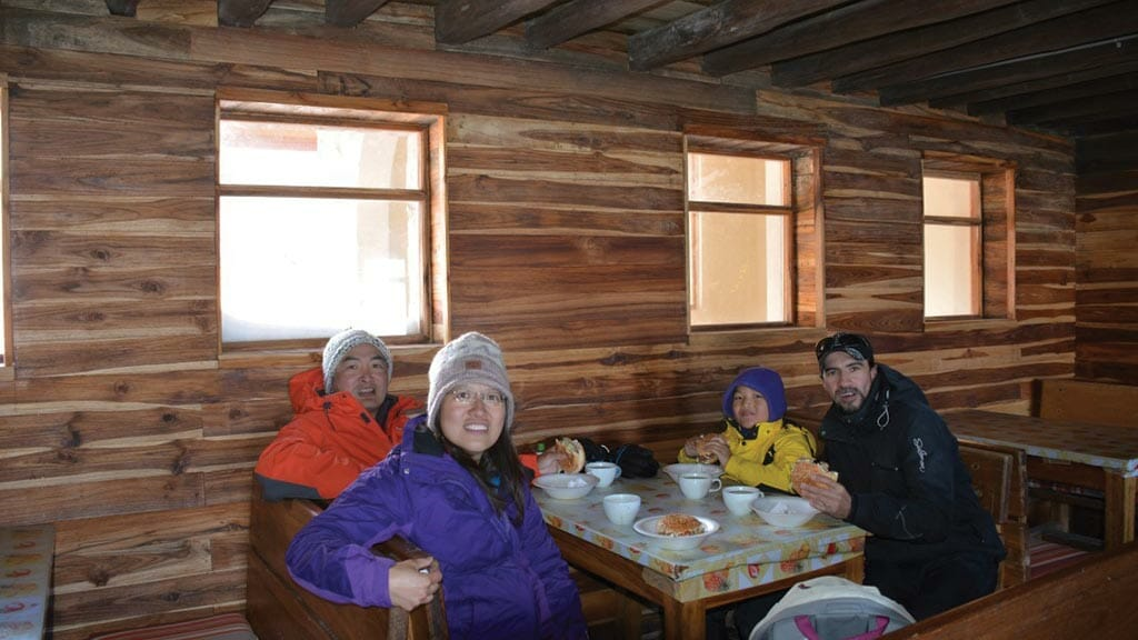 tourists enjoy lunch in the cotopaxi volcano refuge hut