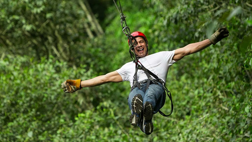 happy tourist enjoying canopy ziplining tour in Mindo cloudforest , Ecuador