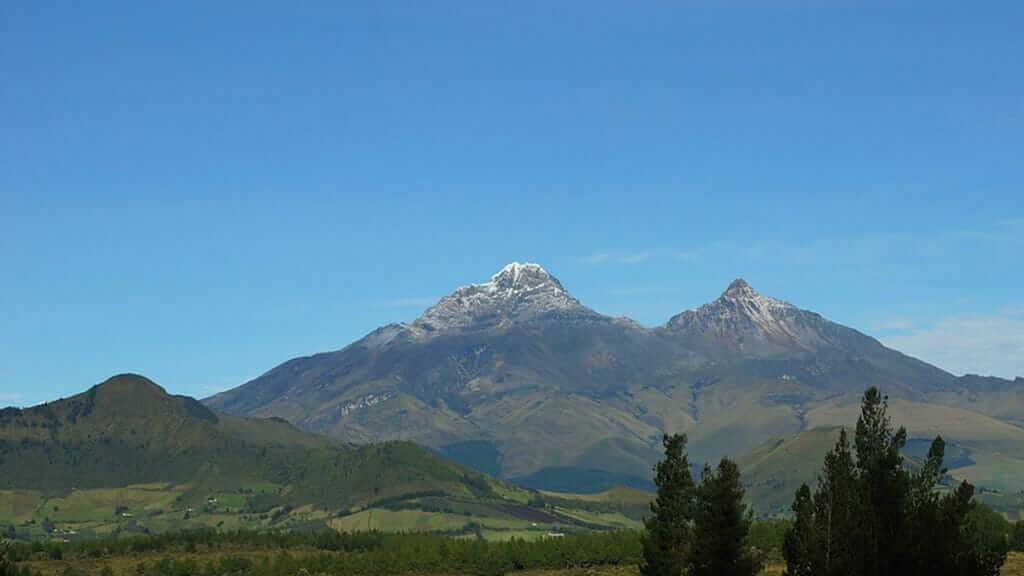 twin peaks of illinizas volcano ecuador with blue sky