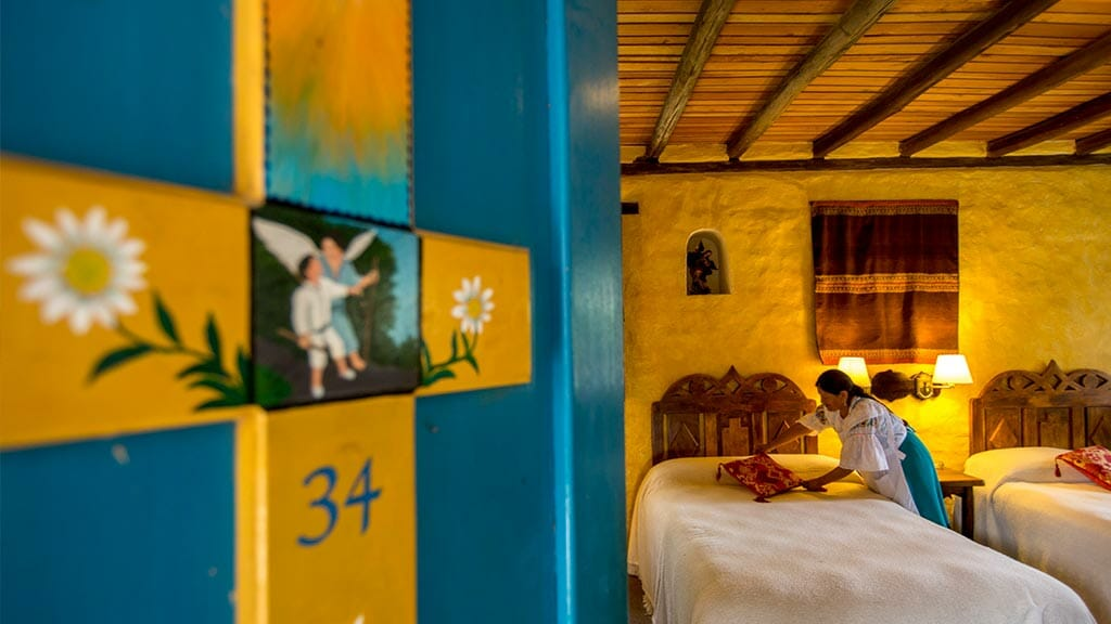 maid makes the bed in hacienda cusin guest bedroom