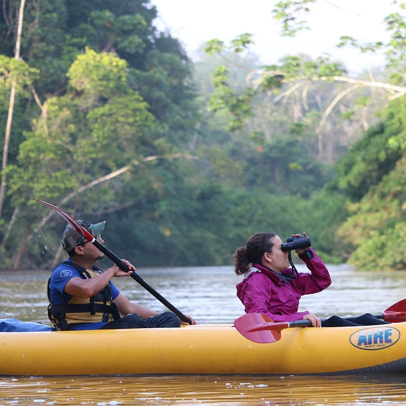 tourist with binoculars on ecuador amazon kayak tour
