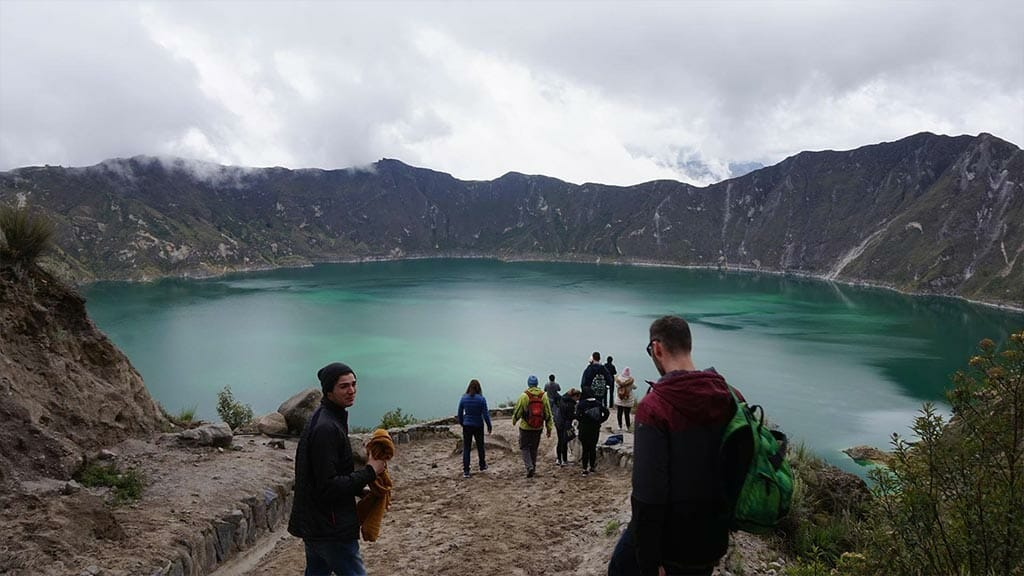 tourists hiking into quilotoa crater ecuador