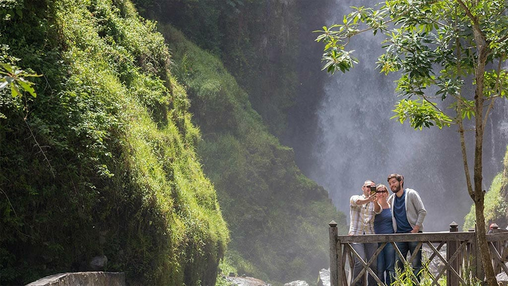 three tourists take a selfie at peguche waterfall otavalo during their ecuador vacation