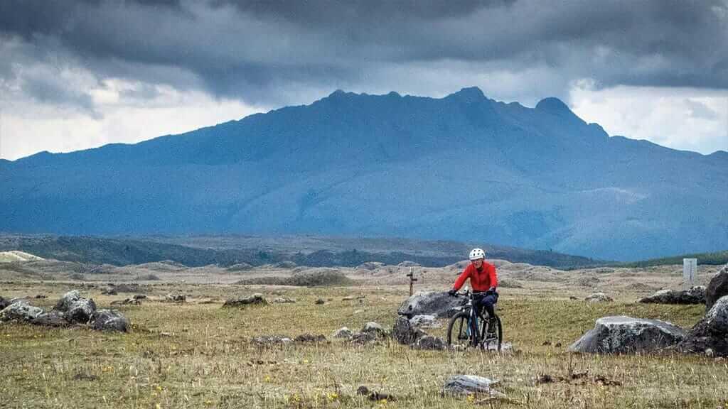 cotopaxi mountain biking tour - a tourist cycles past pasachoa volcano
