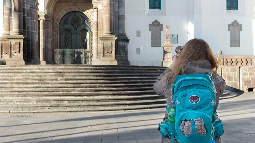 tourist taking photo at the steps of colonial Quito cathedral Ecuador