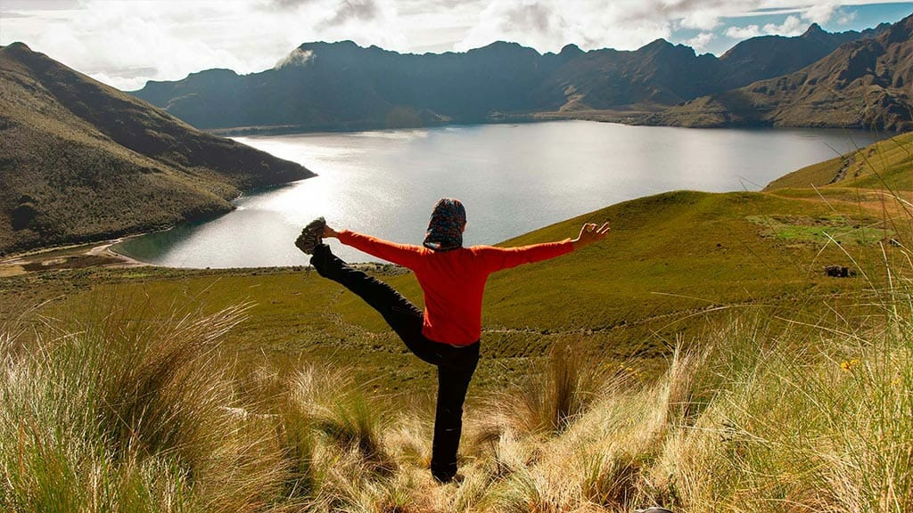 tourist in yoga pose at cuicocha lake otavalo ecuador