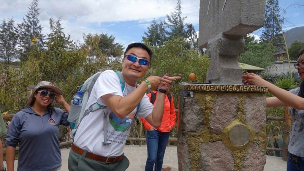 happy tourist balanced an egg on a nail at the equator in quito ecuador inti ñan museum