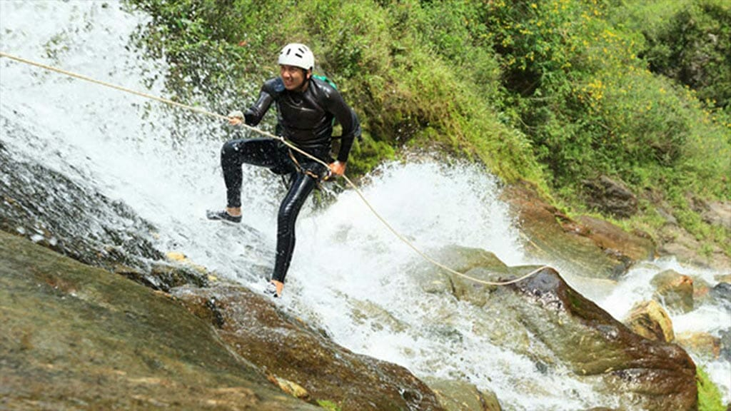 tourist canyoning down a waterfall in ecuador
