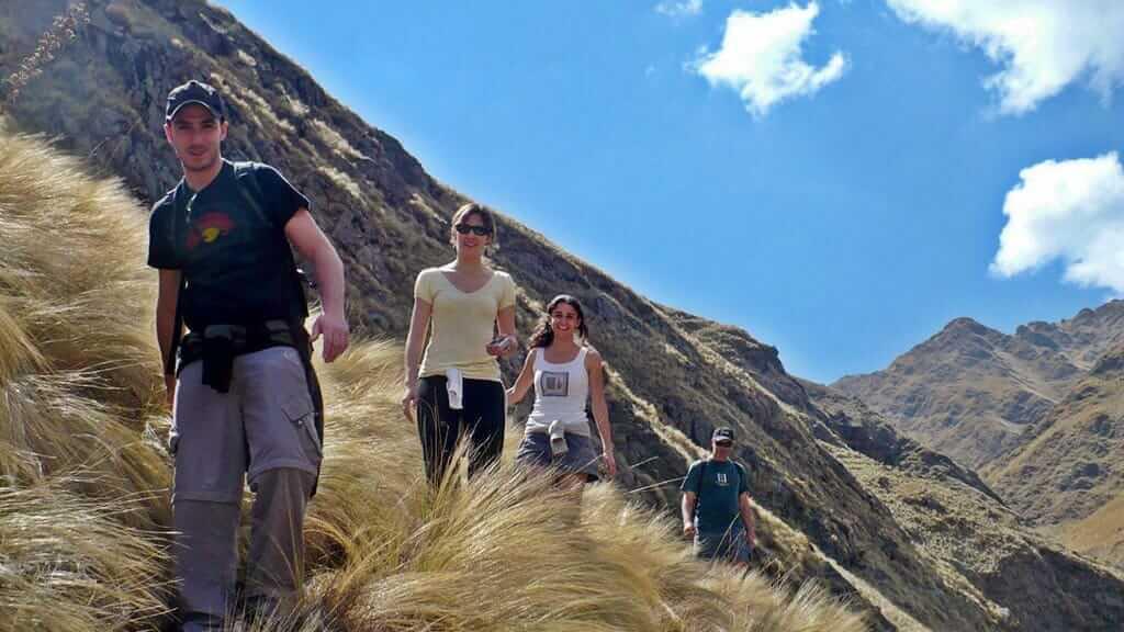 ecuador illinizas treking tour - tourists walk on grassy volcano slope