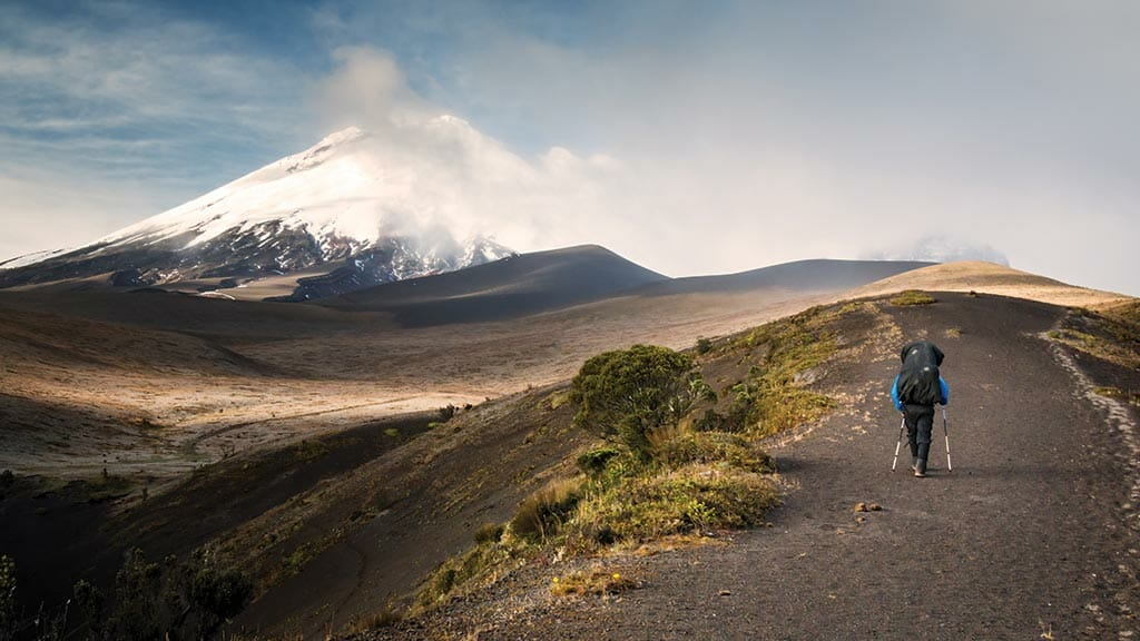 lone hiker on the road to cotopaxi volcano ecuador