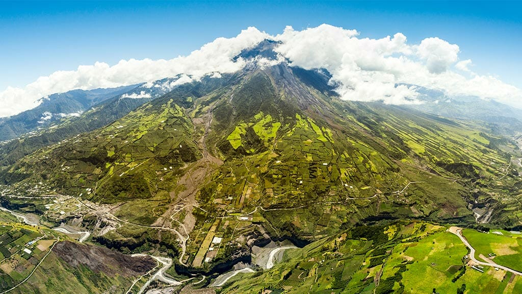 aerial view of tungurahua volcano with green patchwork of fields