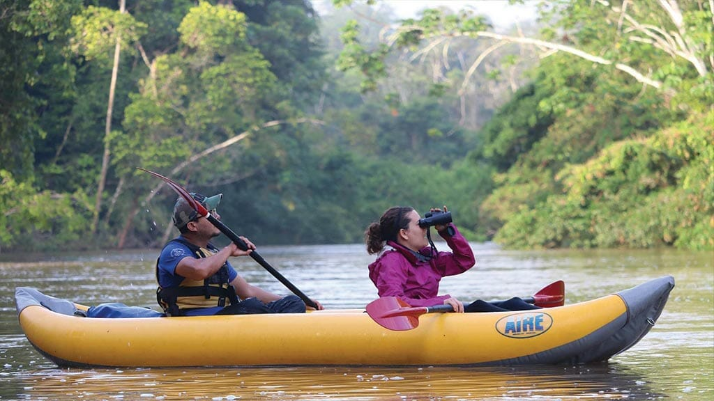tourist with binoculars on ecuador amazon kayak tour