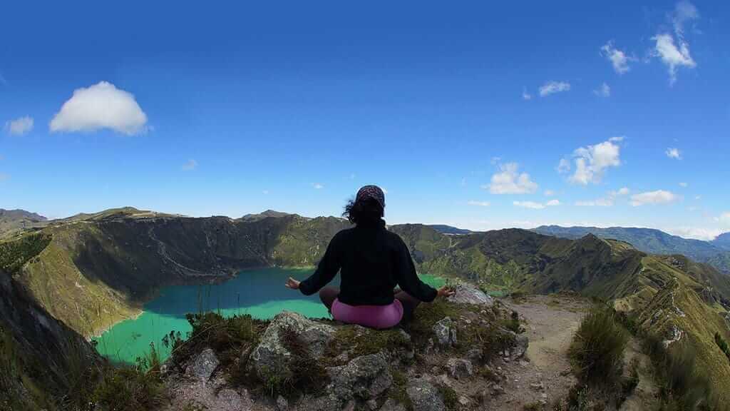 woman making yoga pose at quilotoa crater lake ecuador