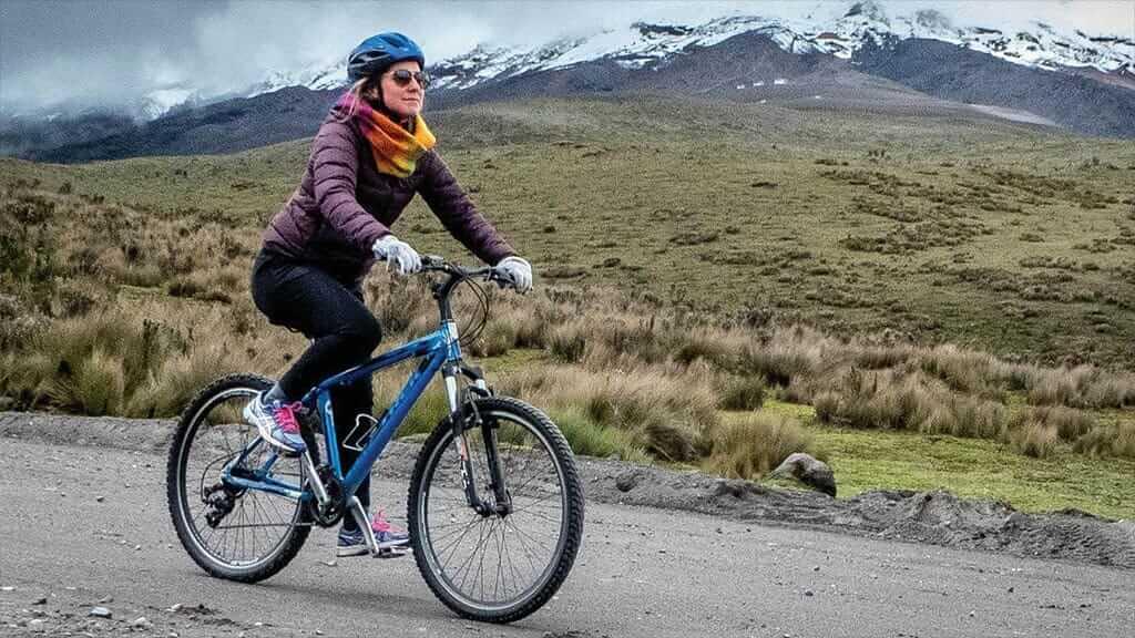woman mountain biking in cotopaxi volcano national park ecuador