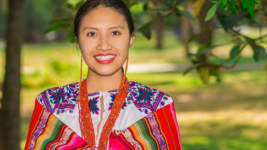 ecuador indigenous woman in colorful traditional dress and jewelerry